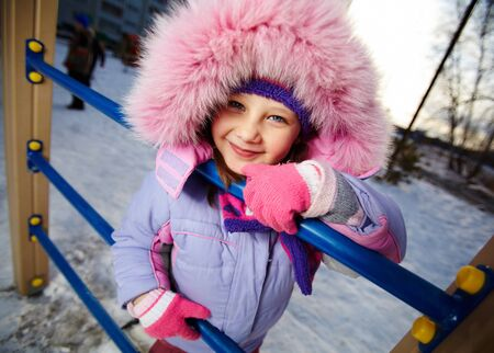 winterwear: Happy girl in winterwear looking at camera while playing outside