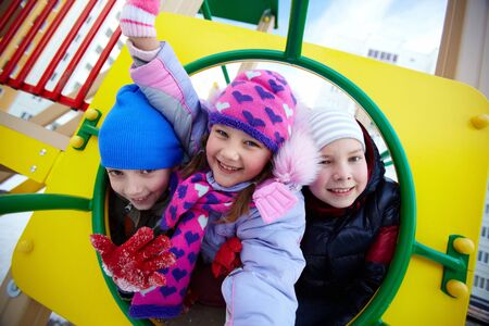 Happy kids in winterwear looking at camera while having fun on playground photo