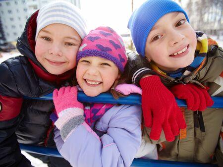 Happy kids in winterwear looking at camera outside photo