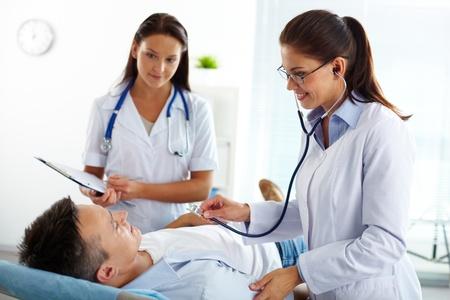 enfermera con paciente: Retrato de dos mujeres médicos mirando a los pacientes durante el tratamiento médico en el hospital