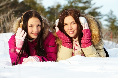 winterwear: Portrait of two pretty girls lying on snow and looking at camera
