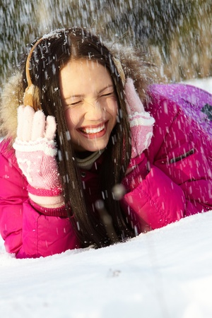 snowdrift: Portrait of pretty girl lying on snow during snowfall Stock Photo