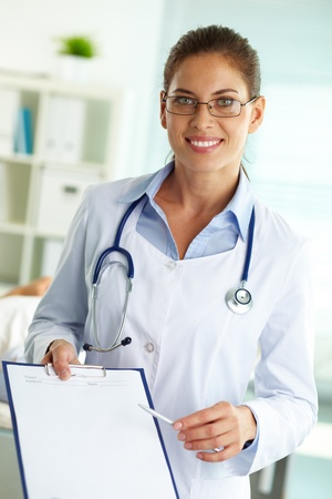 Portrait of confident female doctor with clipboard looking at camera photo