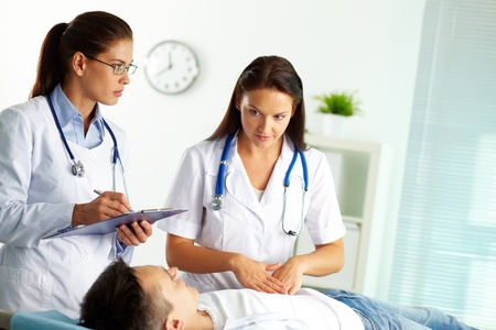 Portrait of confident female doctors during medical treatment of patient in hospital photo