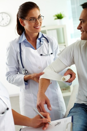 white bandage: Portrait of pretty female doctor giving first aid to patient in hospital