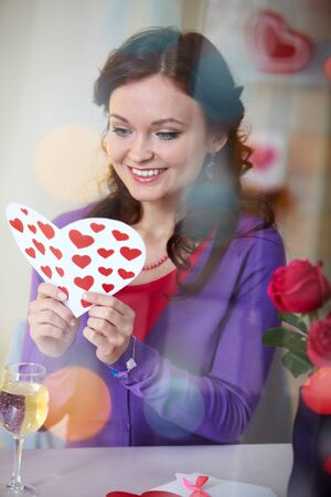 corazon: A young girl in restaurant holding Valentine card  Stock Photo