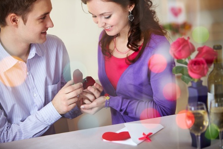 propose: A young man presenting engagement ring to his girlfriend