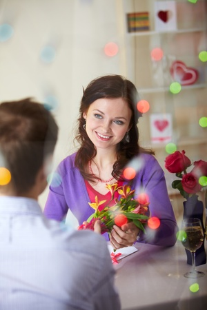 beloved: A young man giving bouquet of flowers to pretty girlfriend
