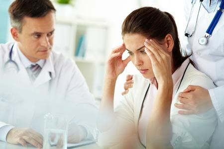 staff medico: Ritratto di donna con mal di testa tocca le tempie con personale medico vicino