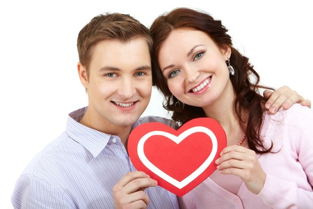corazon: Portrait of a young happy couple holding paper heart