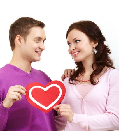 corazon: Portrait of a young beautiful couple holding paper heart and smiling at each other