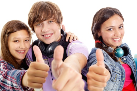 Cute teens with headphones showing thumbs up and smiling at camera photo
