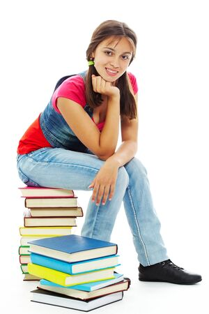 Cute girl sitting on heap of books and looking at camera photo