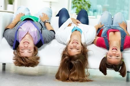 Portrait of three happy friends having fun on sofa photo