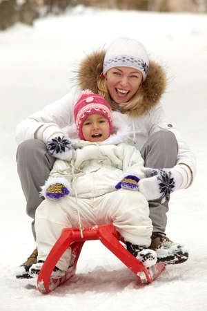 Happy girl and woman in winterwear sitting on sledge in park Stock Photo - 11938242