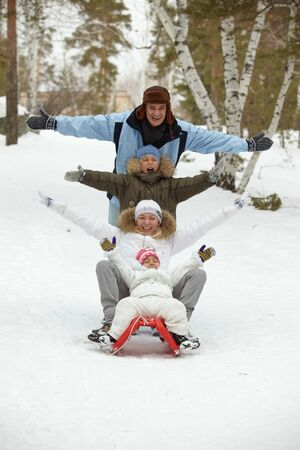 Happy kids and their parents tobogganing in park Stock Photo - 11938226