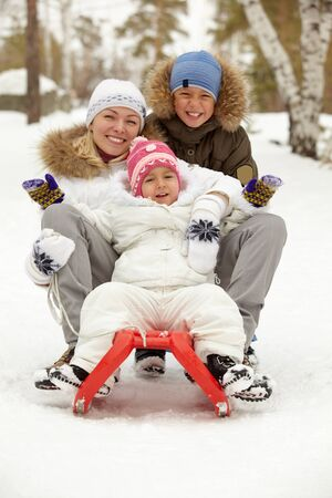 Happy kids and their mother sitting on sledge in park Stock Photo - 11938240