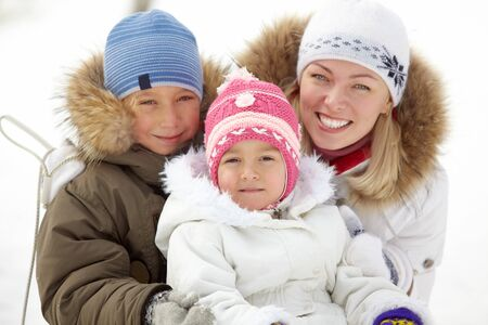 Happy kids and their mother in winterwear looking at camera Stock Photo - 11938231