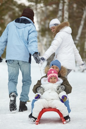 Image of parents riding their kids on sledge in park photo