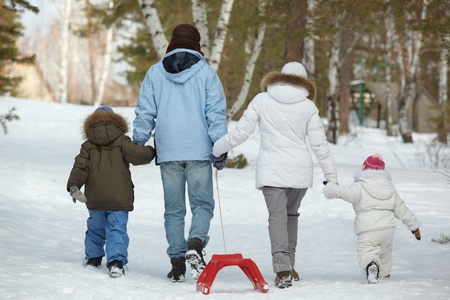 snow girl: Rear view of kids and their parents walking in park Stock Photo