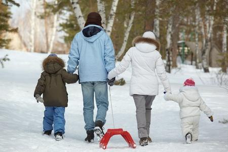 niños caminando: Vista posterior de los niños y sus padres caminando en el Parque Foto de archivo