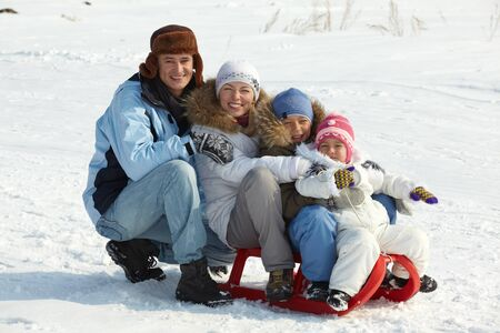 Happy kids and their parents sitting on sledge in park Stock Photo - 11938241
