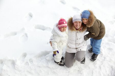 Happy kids and their mother on snow looking at camera Stock Photo - 11938227