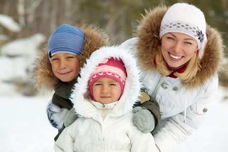 Happy kids and their mother in winterwear looking at camera Stock Photo - 11938247