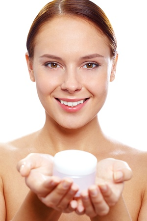 purifying: Fresh woman holding container with facial cream and looking at camera