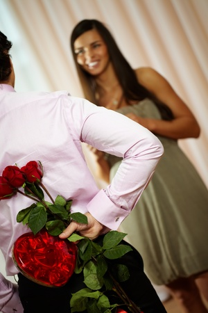 A young man holding bouquet of roses and box of sweets for his girlfriend photo