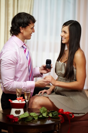 propose: A young man giving engagement ring to his girlfriend while making her proposal Stock Photo