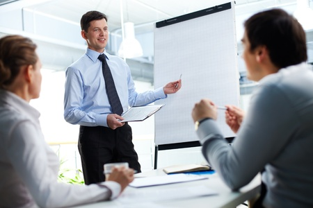 training seminar: Confident businessman and his partners discussing something on a whiteboard Stock Photo