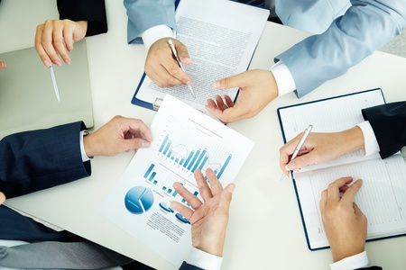 Image of busiess group discussing business documents at meeting photo