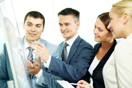 A business man explaining something on a whiteboard to his partners Stock Photo - 11989553
