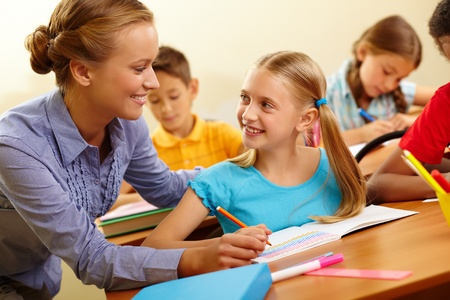 Portrait of smart girl and her teacher looking at each other at lesson in classroom photo