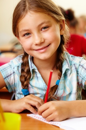 school desk: Portrait of lovely girl drawing in copybook and looking at camera