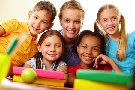 junior education: Portrait of smart schoolchildren and their teacher looking at camera in classroom Stock Photo