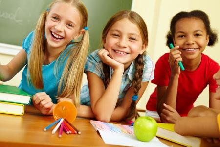 Portrait of joyful schoolgirls laughing in classroom photo