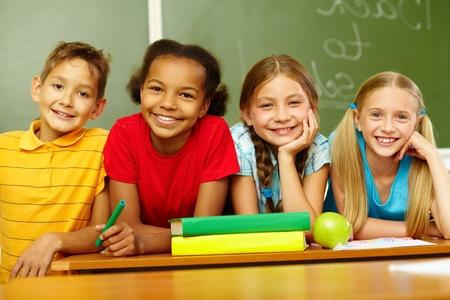 Portrait of cute schoolchildren looking at camera in classroom Stock Photo