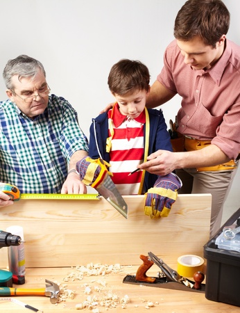 A grandfather and a father teaching a boy to work with diy Stock Photo - 12027378