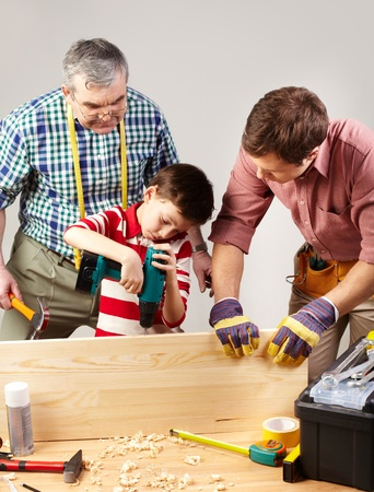 A boy working with drill under his father and grandpa�s supervision photo