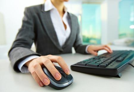 Afbeelding van vrouwelijke handen duwen sleutels van een computer muis en toetsenbord Stockfoto