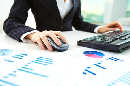 detail internet computer: Image of female hands pushing keys of a computer mouse and keyboard with papers near by Stock Photo