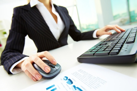 input output: Image of female hands pushing keys of a computer mouse and keyboard with papers near by Stock Photo