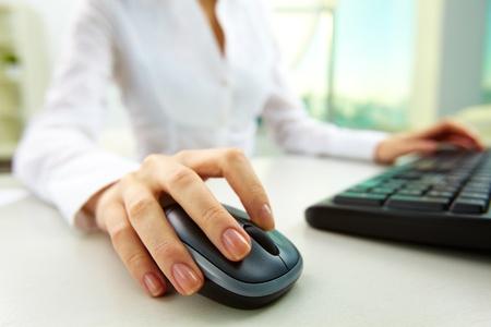 Imagen de las manos femeninas que empujan las teclas de un ratón de ordenador y el teclado Foto de archivo