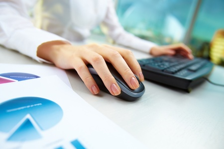 Image of female hands pushing keys of a computer mouse and keyboard with papers near by Stock Photo - 11988685