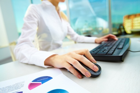paypal: Image of female hands pushing keys of a computer mouse and keyboard with papers near by Stock Photo