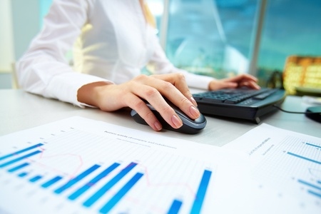 ebusiness: Image of female hands pushing keys of a computer mouse and keyboard with papers near by Stock Photo