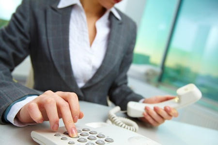 telephony: Female hand holding phone receiver and dialing number Stock Photo