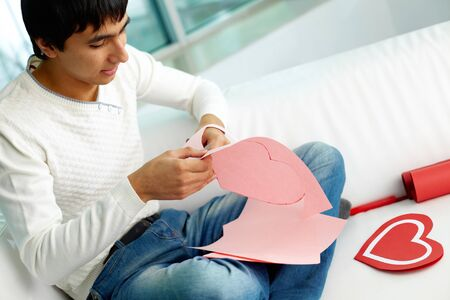 Image of handsome man cutting paper heart before St. Valentine day Stock Photo - 12008975